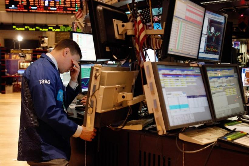 A specialist trader rubs his eyes as he works on the floor of the New York Stock Exchange