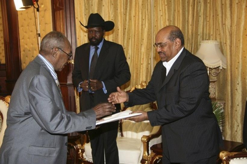 Southern Sudan Referendum Commission (SSRC) chairperson Mohamed Ibrahim Khalil (L) hands out the results of the referendum to Sudan's President Omar Hassan Al Bashir.