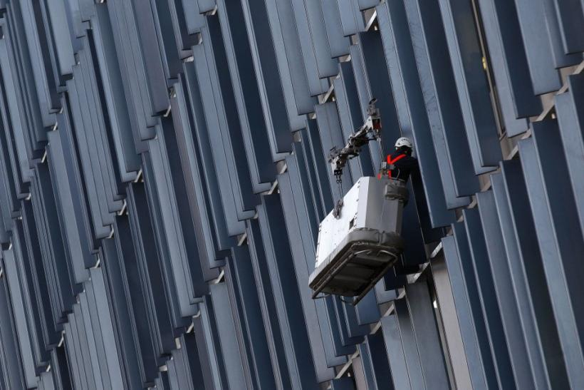 A worker cleans windows on a building in London
