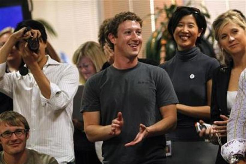 "Facebook CEO Zuckerberg applauds while unveiling the company's new ""places"" feature during a news conference in Palo Alto"
