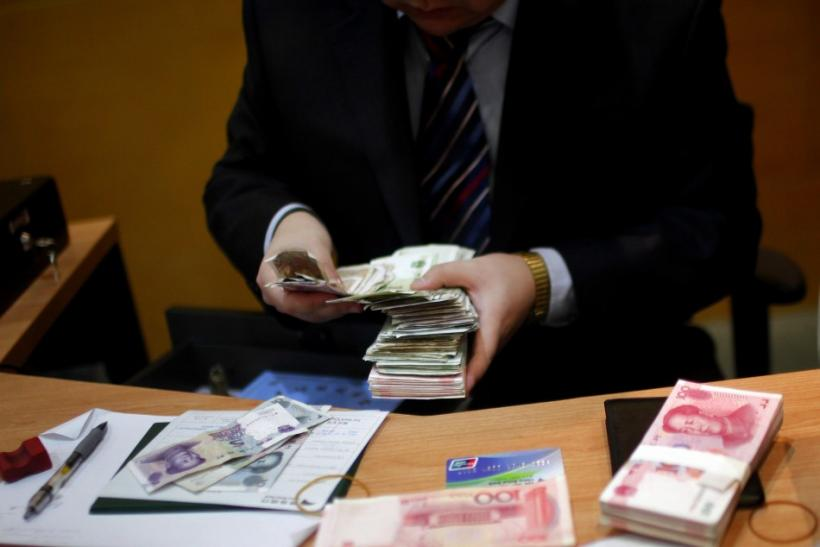 Employee counts Yuan currency at a local bank in Shanghai