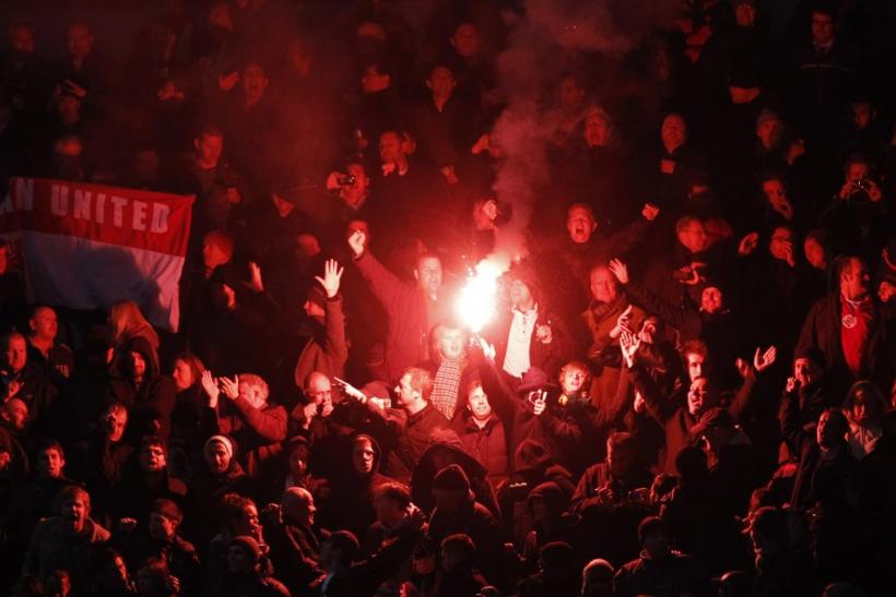 Manchester United fans hold up a flare.