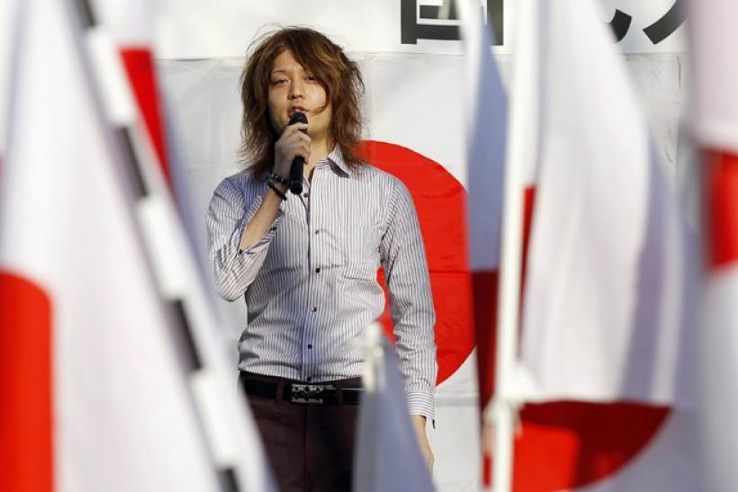 Political activist Tsunehira Furuya, 28, speaks on a podium during a rally