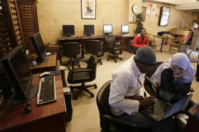 People sit in an internet cafe in Cairo