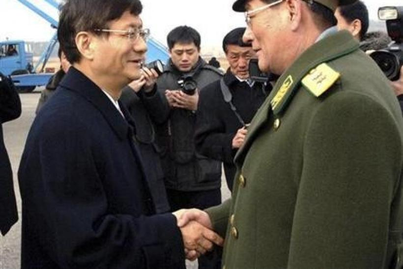 China's public security minister Meng Jianzhu (L) is greeted by North Korean official upon his arrival at an airport in Pyongyang in this picture released by North Korea's official KCNA