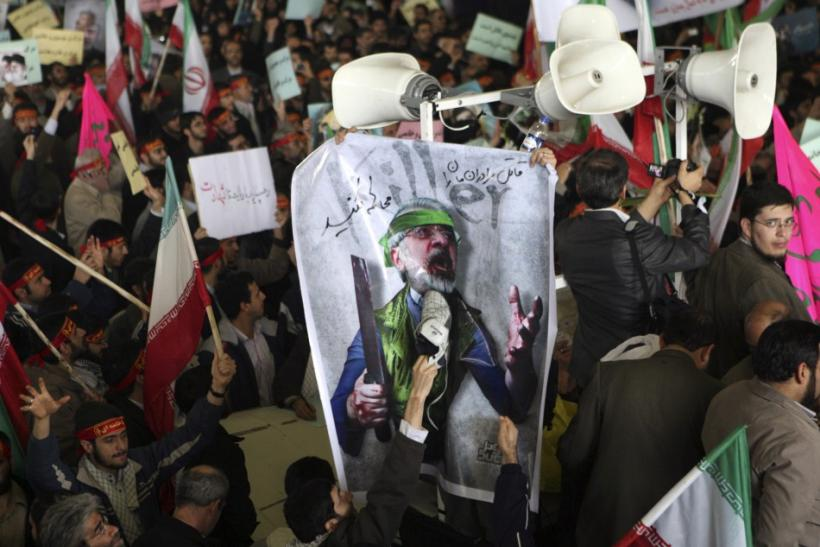 A man uses his shoe to hit a poster of reformist opposition leader Mirhossein Mousavi during the funeral of student Sanea Jaleh in Tehran