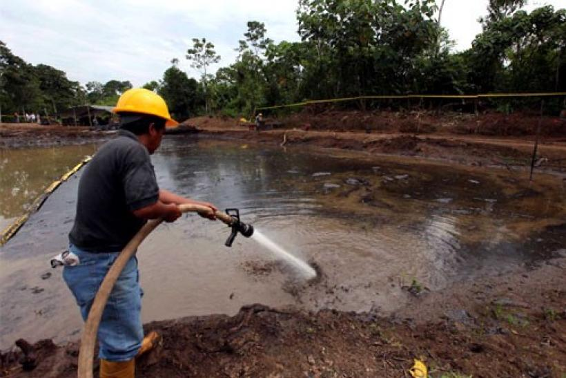 Ecuadorean workers clean up an oil waste pit owned by state petroleum company Petroecuador in Shushufindi, east of Quito, December 8, 2009