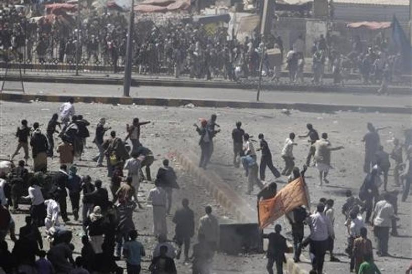 Anti-government protesters (back to the camera) and government backers face each other during clashes in Sanaa