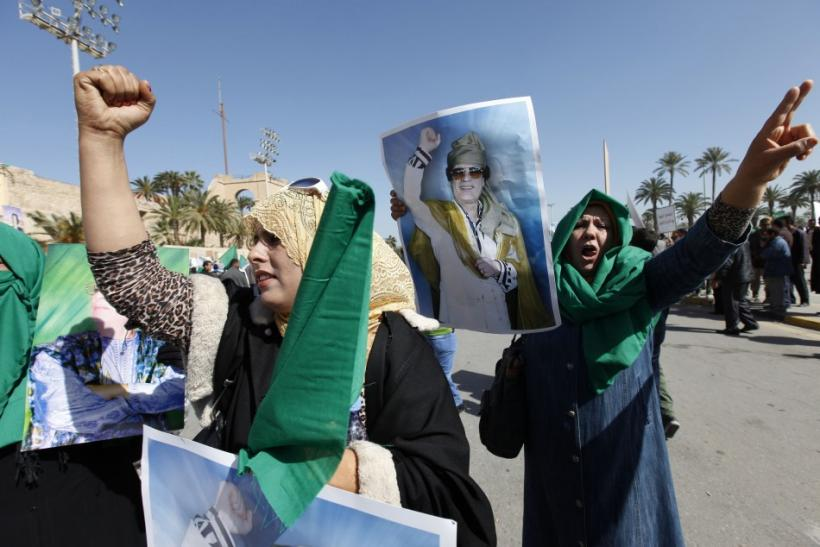 Pro-government supporters hold posters of Libyan leader Gaddafi as they chant slogans during a demonstration in Tripoli