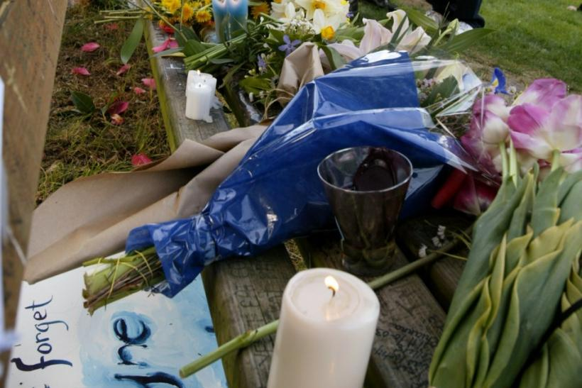 Fans look at an informal memorial of flowers, candles and artwork placed on a park bench at Viretta Park in Seattle, Washington