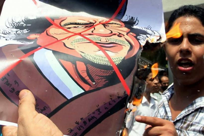 A Libyan living in Malaysia burns a cartoon image of Libyan leader Muammar Gaddafi during a protest in Kuala Lumpur