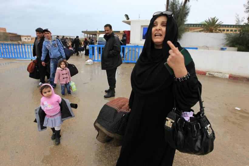 A Tunisian woman reacts as she crosses the border into Tunisia at the border crossing of Ras Jdir after fleeing unrest in Libya