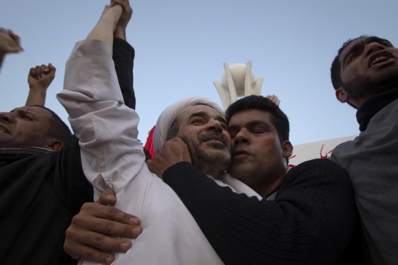 Cleric Sheikh Mohammed Habib Muqdad, on of the prisoners pardoned by Bahrain's King Hamad bin Isa, is kissed by a supporter on the protesters' stage at Pearl Square in Manama