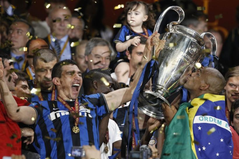Inter Milan's Lucio and Maicon celebrate with the trophy following their team's Champions League final soccer match victory against Bayern Munich at the Santiago Bernabeu stadium in Madrid, May 22, 2010.
