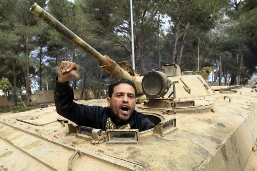 A man gestures as he sits in an army armoured vehicle in Shahat