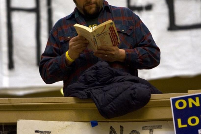 A union worker reads a book inside the state capitol during the eighth day of protests against the proposed bill by Governor Scott Walker in Madison, Wisconsin February 22, 2011.
