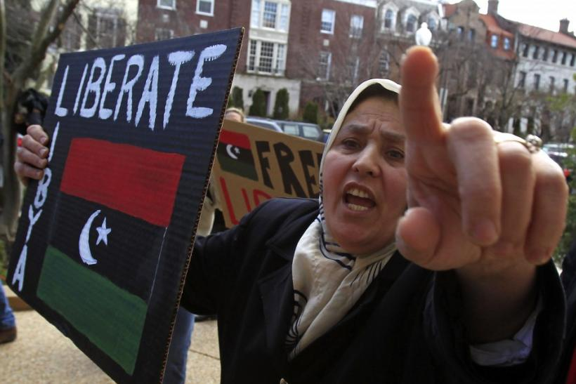 A Libyan-American woman gestures while holding a placard during a protest against Muammar Gaddafi, at the residence of the Libyan ambassador, in Washington