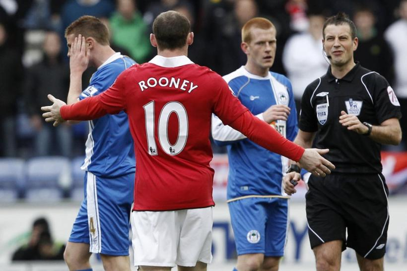 Rooney gestures towards referee Clattenburg after clashing with Wigan Athletics' McCarthy during their EPL soccer match in Wigan