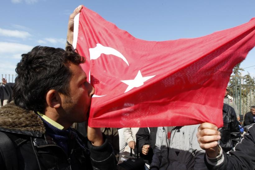 A Turkish worker kisses the Turkish flag at the Libyan and Tunisian border crossing of Ras Jdir after fleeing unrest in Libya