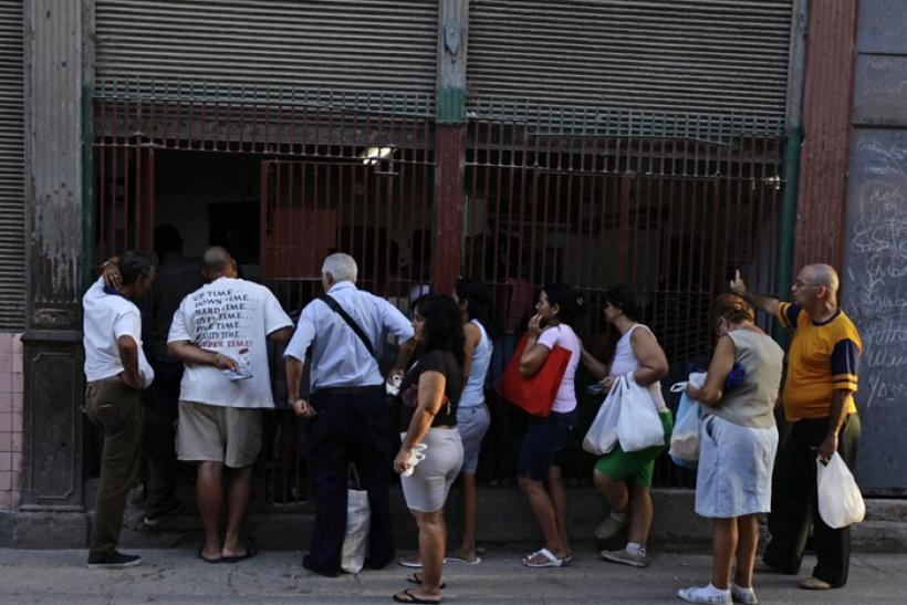 People queue at a state food outlet or 'bodega' on a street of Havana