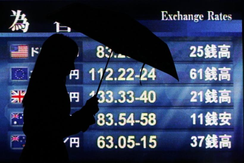 Woman holding an umbrella is silhouetted against a board displaying exchange rates outside a brokerage in Tokyo