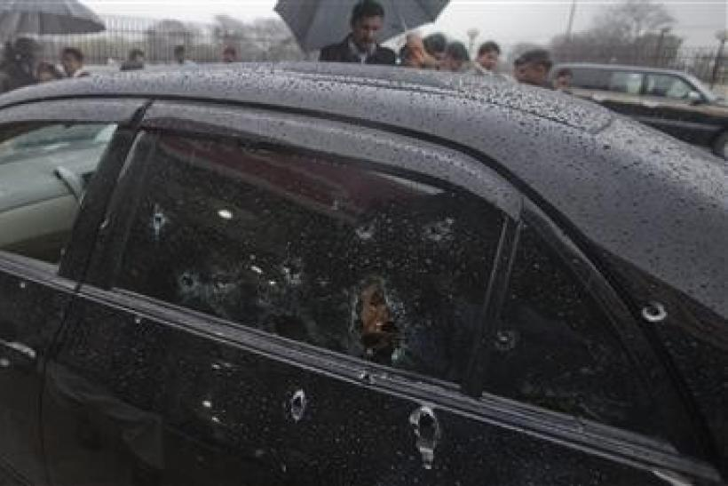 Security officials examine the bullet-riddled car of slain Pakistan's Minister for Minorities Shahbaz Bhatti