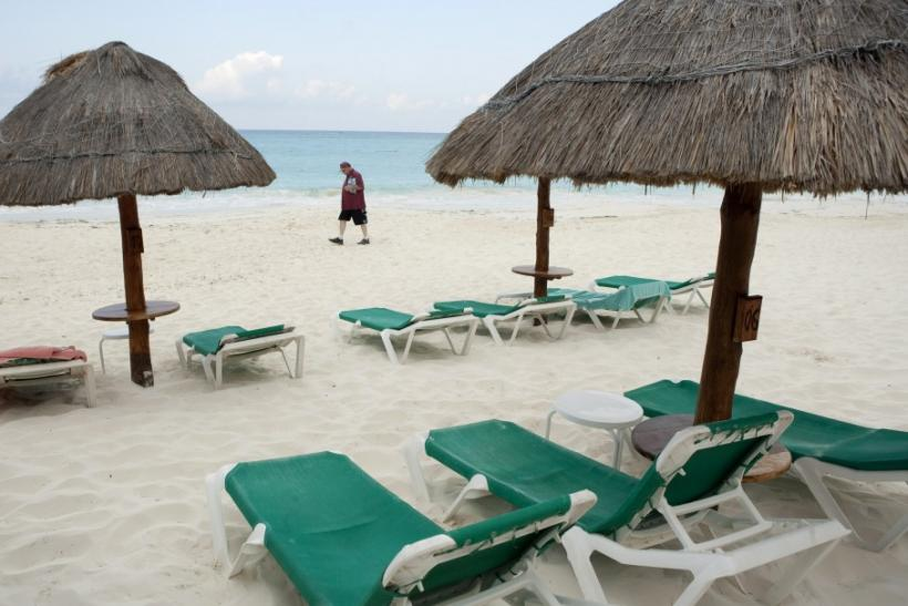 Tourist walks past empty beach chairs in Cancun
