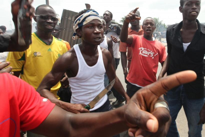 Anti-Gbagbo protester stands with knife near a roadblock and burning tyres in the Abobo area of Abidjan