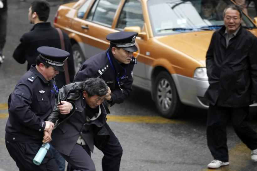 "Police arrest a man in front of the Peace Cinema in downtown Shanghai, after calls for a ""Jasmine Revolution"" protest"