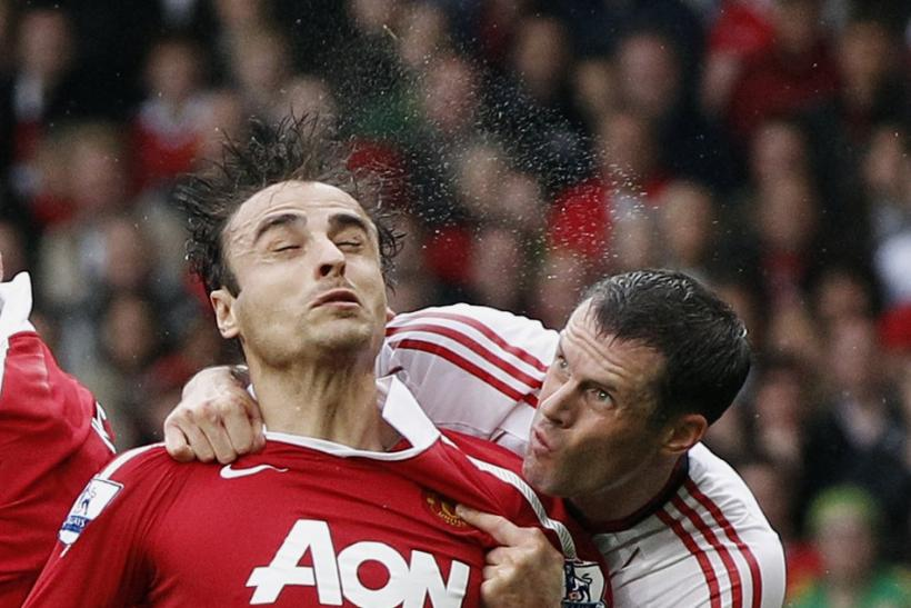 Manchester United's Berbatov challenges Liverpool's Carragher during their English Premier League soccer match at Old Trafford in Manchester.