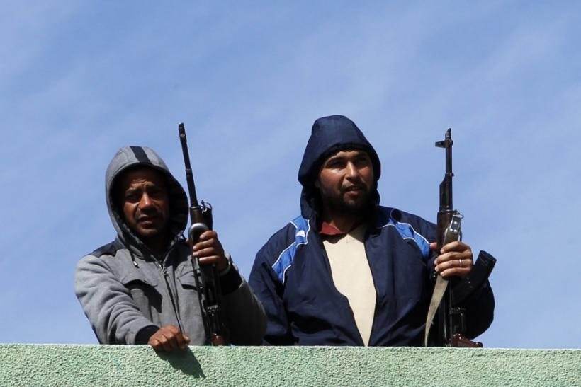 Gunmen opposed to leader Muammar Gaddafi stand guard on a rooftop in the centre of the city of Zawiyah