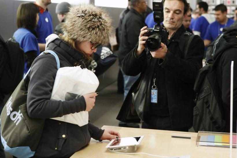A woman inspects one of Apple's iPad 2 tablets at the company's flagship 5th Ave store in New York