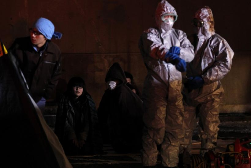 Officials in protective gear stand next to people who are from the evacuation area near the Fukushima Daini nuclear plant, in Koriyama