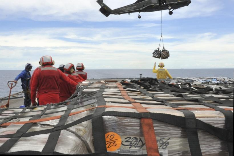 US sailors aboard the U.S. 7th Fleet command ship USS Blue Ridge stand-by to move pallets of humanitarian relief supplies