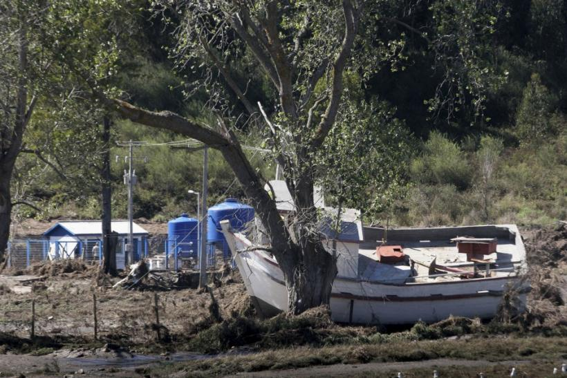A damaged boat is seen after being dragged onto dry land by a tsunami which hit a small bay of Coliumo