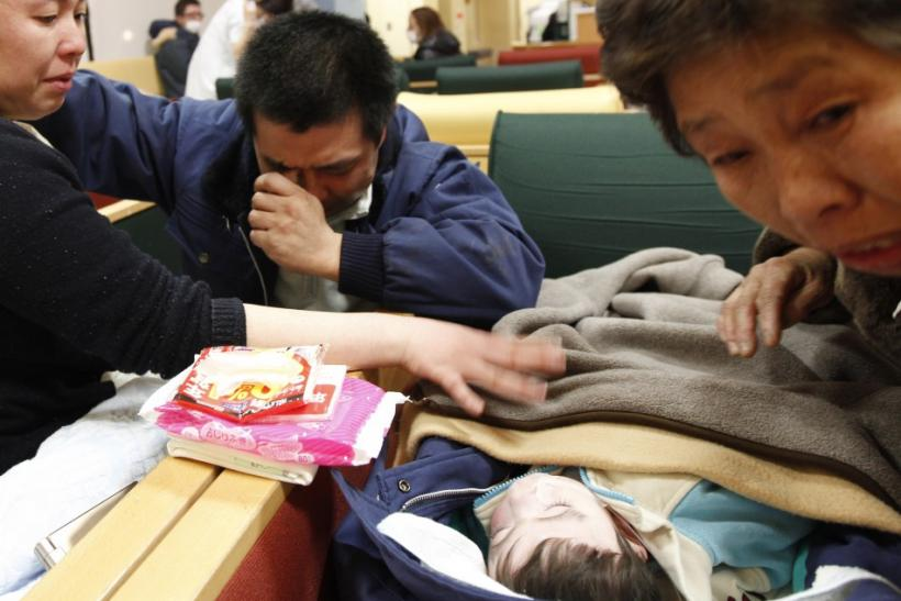 A man reacts as he finds his wife and child at the Red Cross hospital after they were separated by earthquake and tsunami, in Ishinomaki,