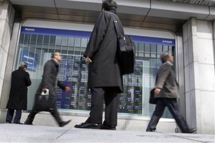 People look at a screen displaying stock prices in Tokyo
