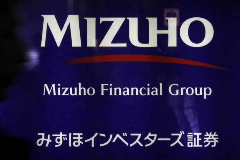 A man passes a logo of the Mizuho Financial Group in Tokyo