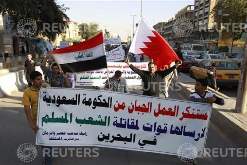 Residents hold up Bahraini and Iraqi flags during a demonstration in central Baghdad.