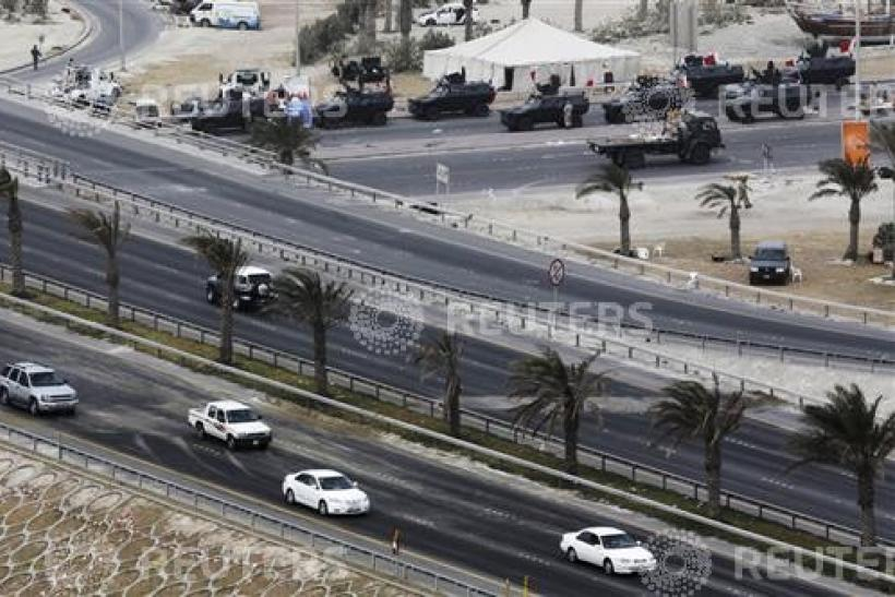 Cars drive on Pearl Square flyover after protesters were cleared in a crackdown in Manama
