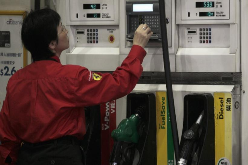 A worker checks the price of fuel at a gas station in Hong Kong January 14, 2011.