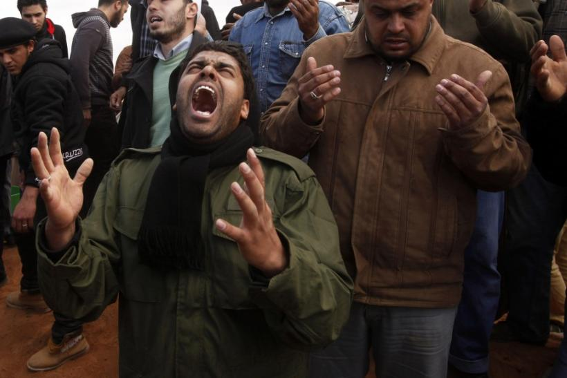 Mourners react next to grave of a rebel killed by forces loyal to Libyan leader Muammar Gaddafi in Ajdabiyah, during his funeral in Benghazi