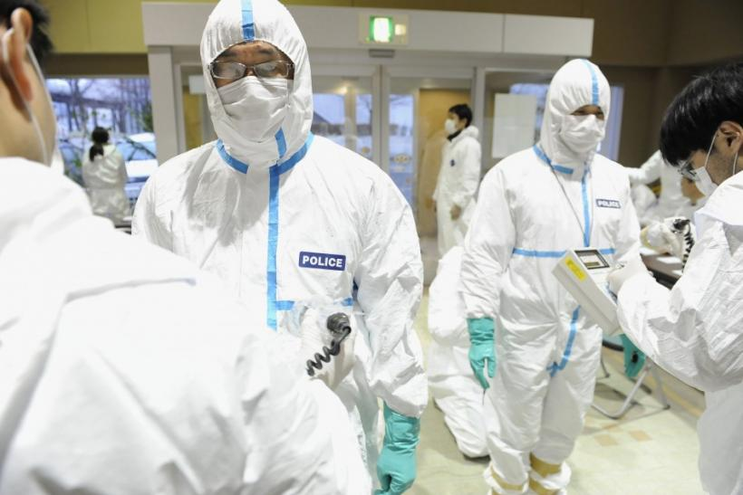 Police who have finished measuring radiation are screened for radiation contamination in Kawamata