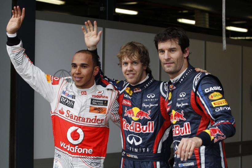 Red Bull driver Vettel of Germany, teammate Webber of Australia and McLaren's Hamilton of Britain pose for photographers after the qualifying session of the Australian F1 Grand Prix in Melbourne.