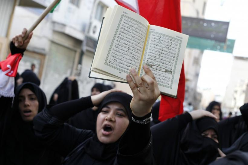 A Bahraini woman holds a Koran over her head as she shouts anti-government slogans during a protest in the mainly Shi'ite village of Diraz
