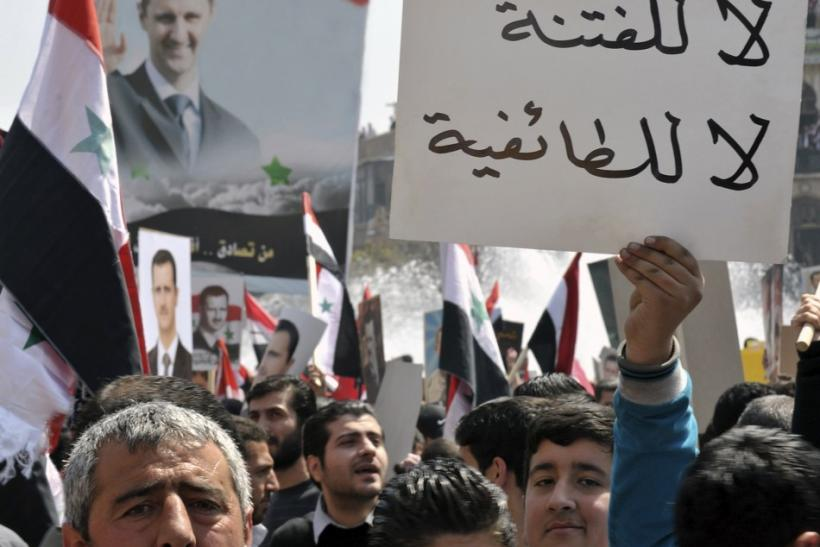 A pro-government demonstrator holds up a placard during a rally at the central bank square in Damascus