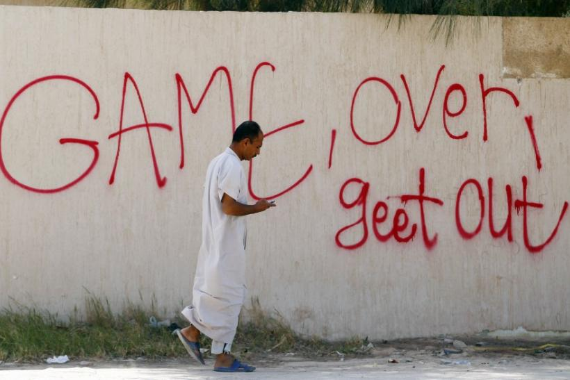 A man walks past graffiti in the town of Ajdabiyah
