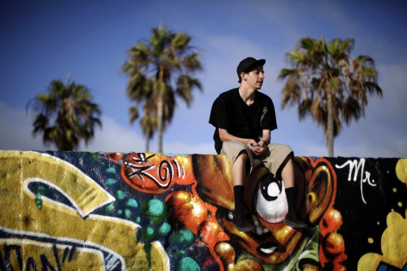 A teenager sits on a wall on Venice Beach in Los Angeles