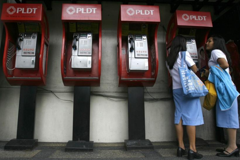 Students use a pay phone on the street in Manila