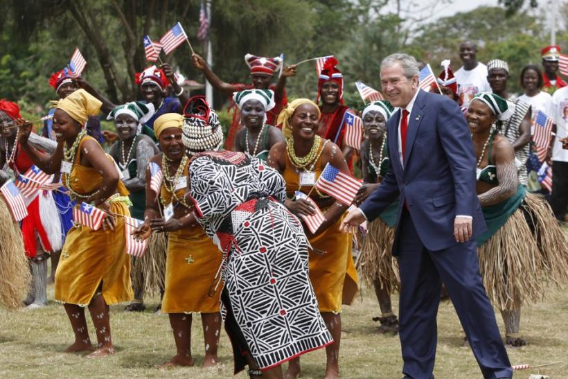 U.S. President Bush dances with performers in Monrovia